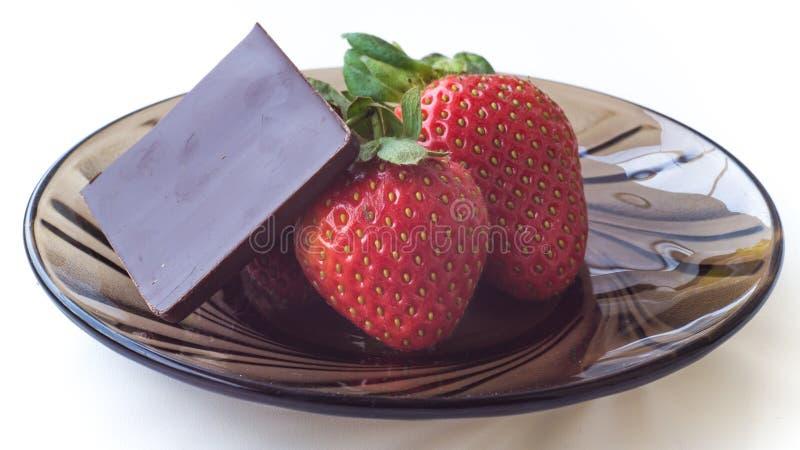Mogna jordgubbar och choklad på en glass platta royaltyfri bild