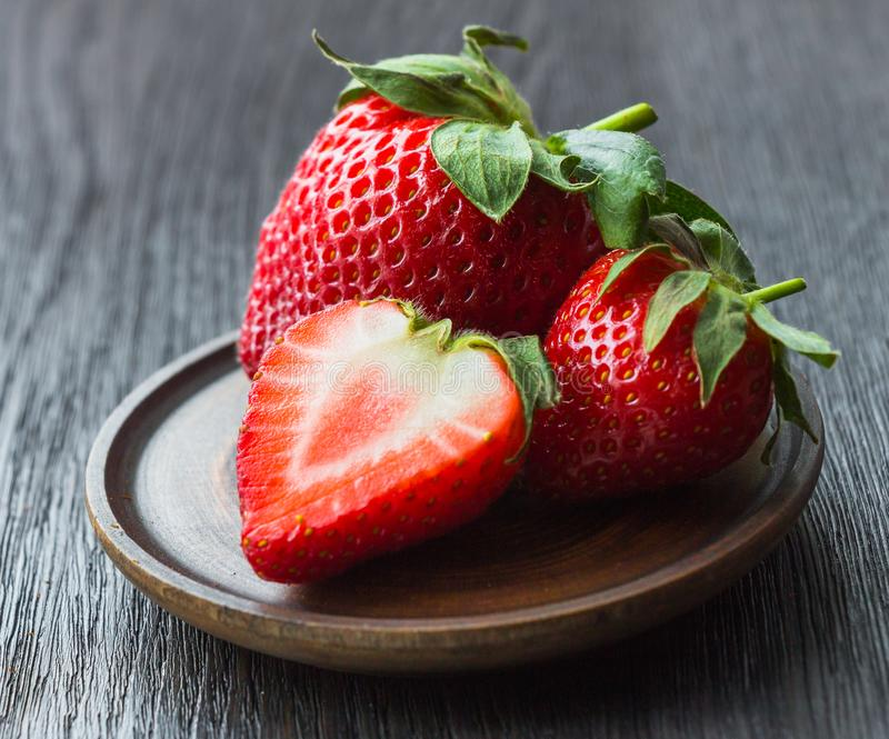 Mogna jordgubbar, rött, helt, halva, närbild på en mörk bakgrund arkivbild