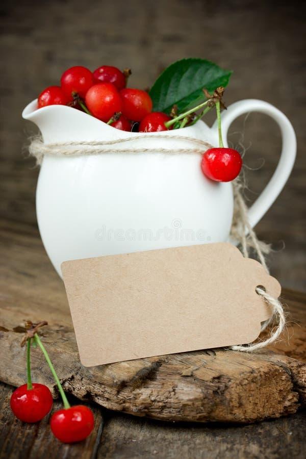 Mogna körsbär i en vit krus med etiketten för brunt papper royaltyfria bilder