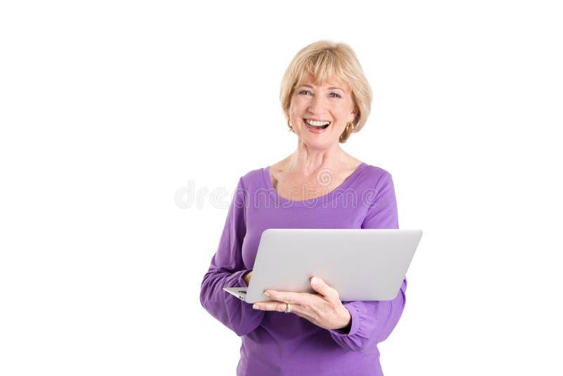 Mogna kvinnan som använder bärbara datorn för att shoppa direktanslutet royaltyfri bild