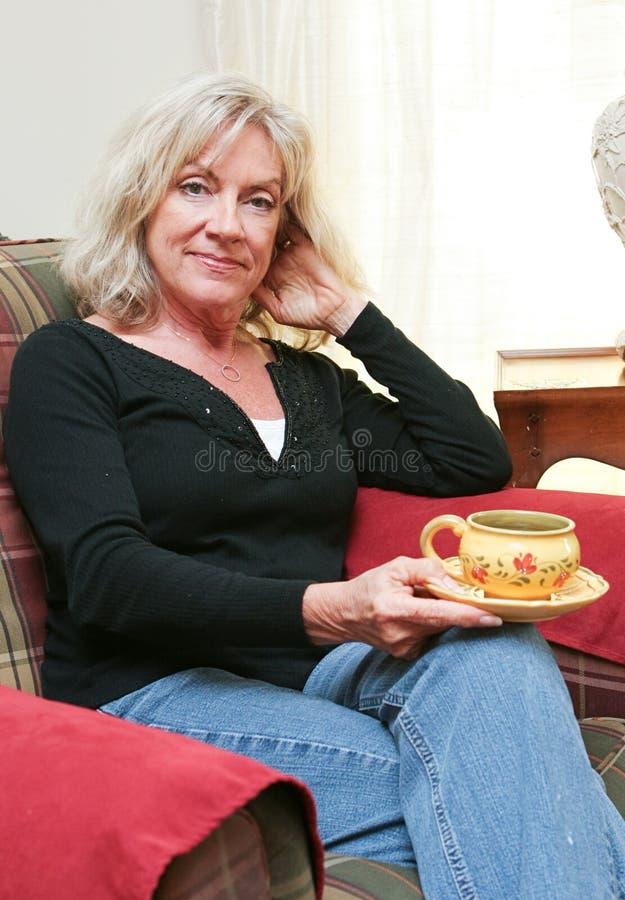 Mogna kvinnan som hemma kopplar av arkivfoton