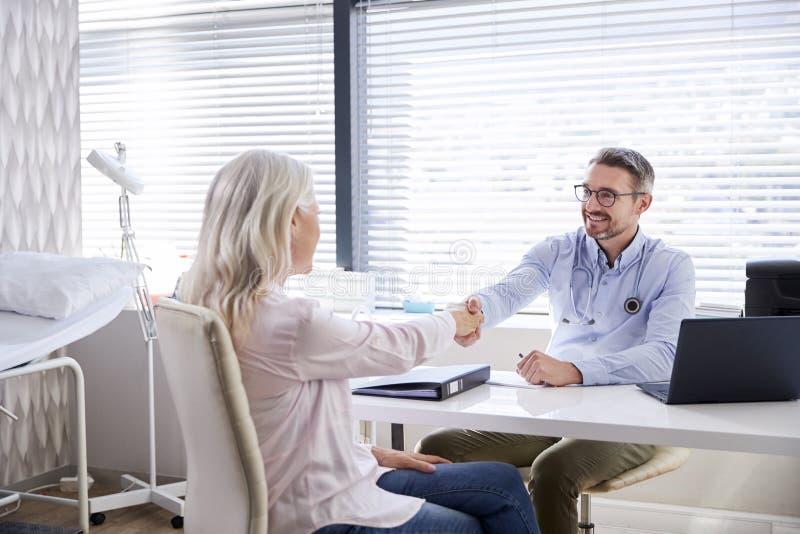 Mogna kvinnliga tålmodiga skaka händer med doktor Sitting At Desk i regeringsställning royaltyfri fotografi