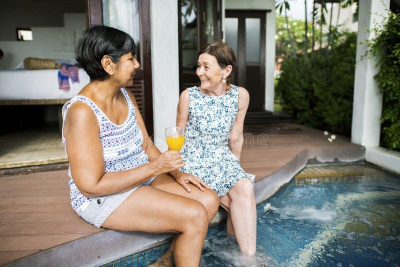 Mogna kvinnliga vänner på en semesterort royaltyfri fotografi