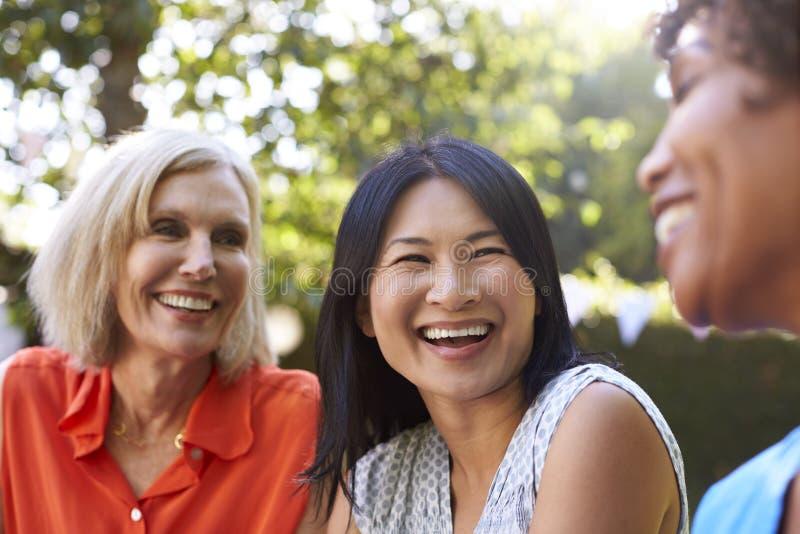 Mogna kvinnliga vänner som tillsammans umgås i trädgård royaltyfria foton