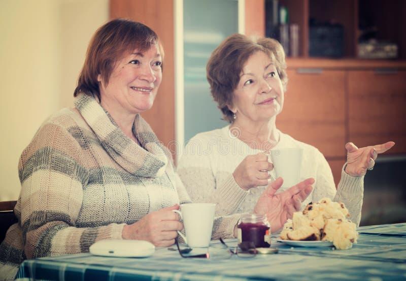 Mogna kvinnor som håller ögonen på film och inomhus dricker te arkivbild