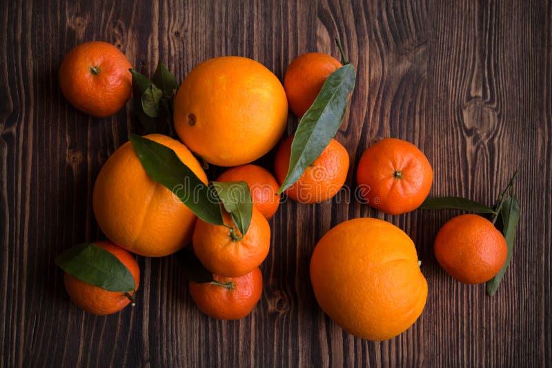 Mogna läckra mandarines och apelsiner på den mörka trätabellen arkivfoton