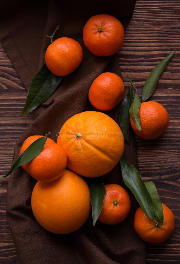 Mogna läckra mandarines och apelsiner på den mörka trätabellen royaltyfria foton