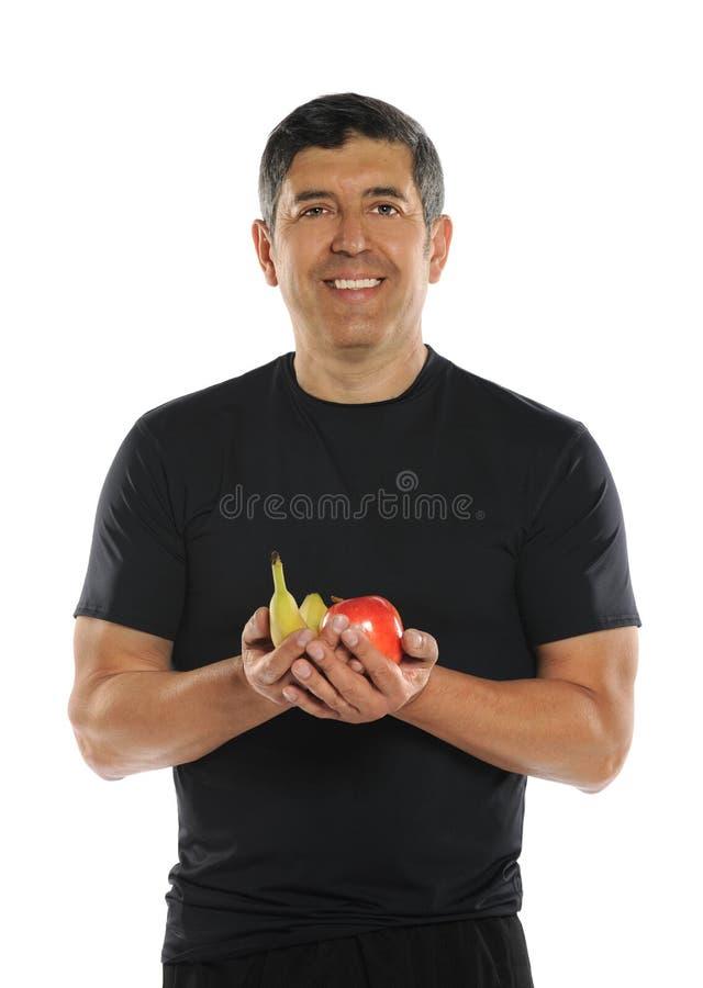 Mogna latinamerikanska manHoldingfrukter arkivfoto