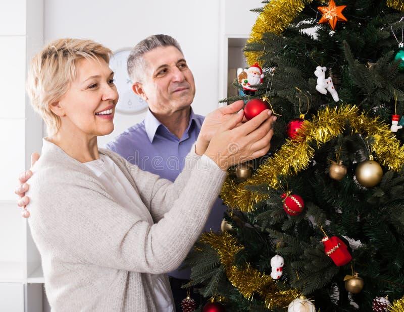 Mogna lyckliga par dekorerar gran-trädet för ferier av jul arkivbild