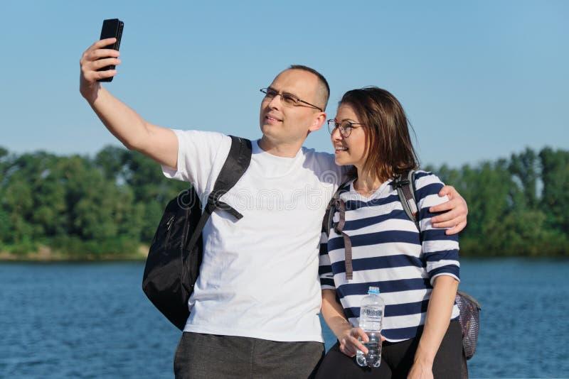 Mogna lyckliga par som tar selfiefotoet på telefonen, folket som kopplar av nära floden i sommarafton, parkerar fotografering för bildbyråer