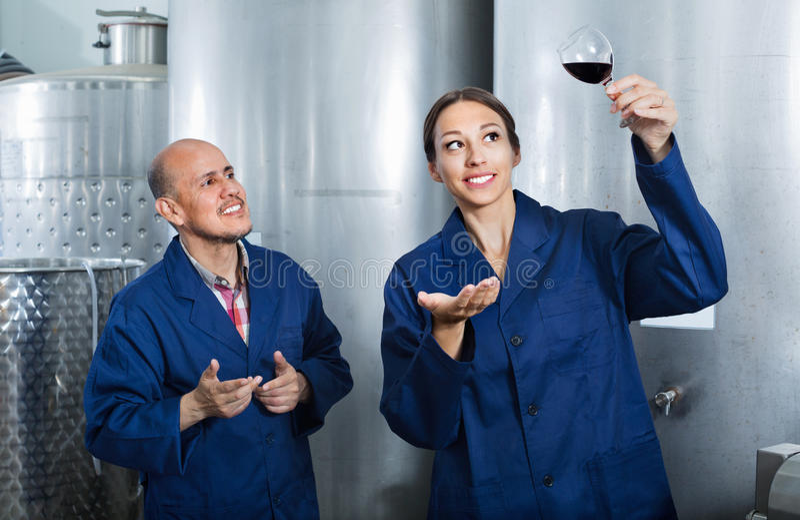 Mogna man- och kvinnacoworkers som ser vin i exponeringsglas royaltyfri fotografi