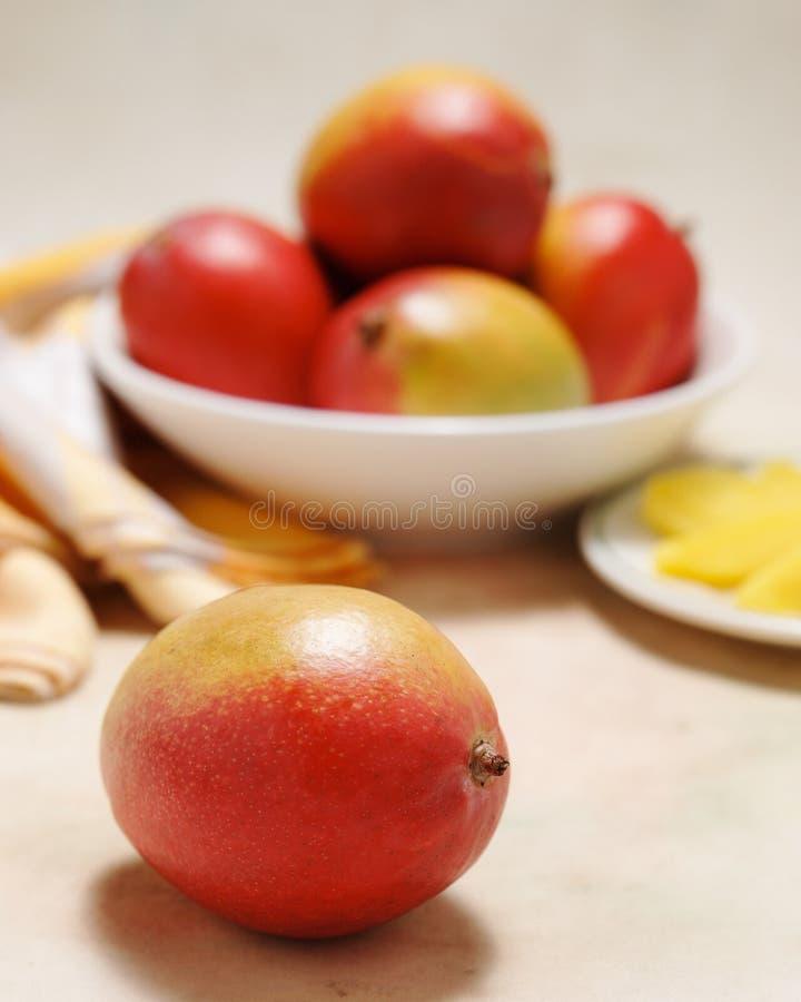 Mogna mango i en bunke med plattan av klippt frukt på en slappt kulör tabelltorkduk royaltyfria foton
