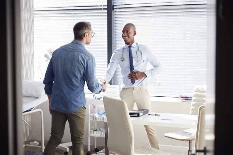 Mogna manliga tålmodiga skaka händer med doktor In Office royaltyfri bild