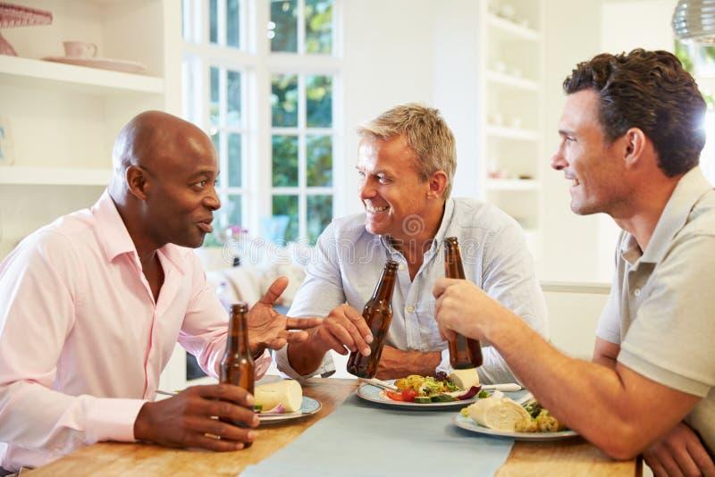 Mogna manliga vänner Sit At Table Drinking Beer och äta royaltyfria foton