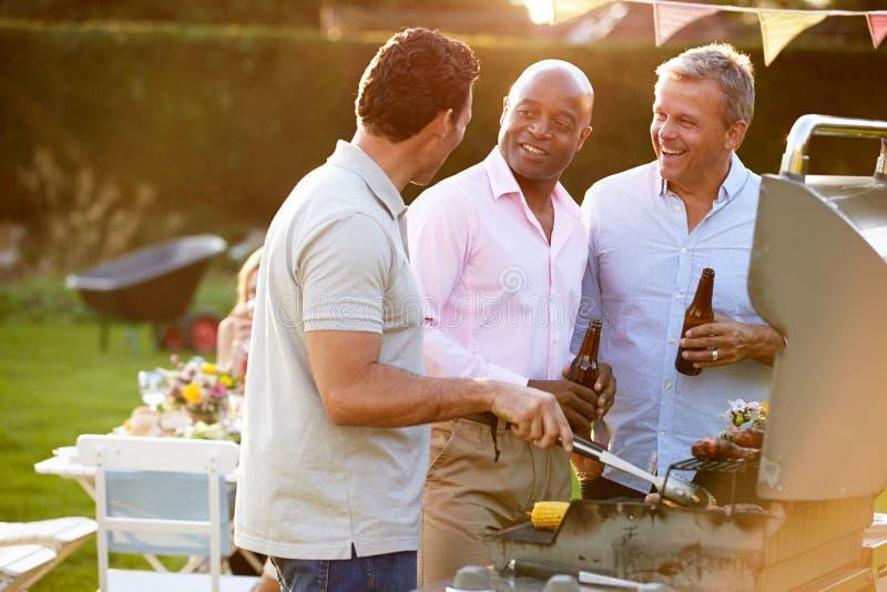 Mogna manliga vänner som tycker om den utomhus- sommargrillfesten royaltyfria bilder