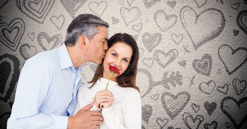 Mogna mannen som kysser, medan ge en röd ros till kvinnan fotografering för bildbyråer