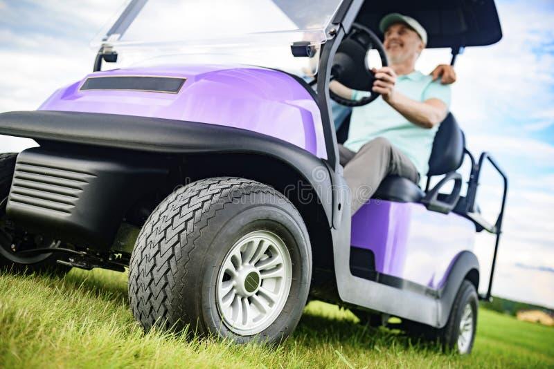 Mogna mannen som ler, medan köra golfvagnen arkivfoton