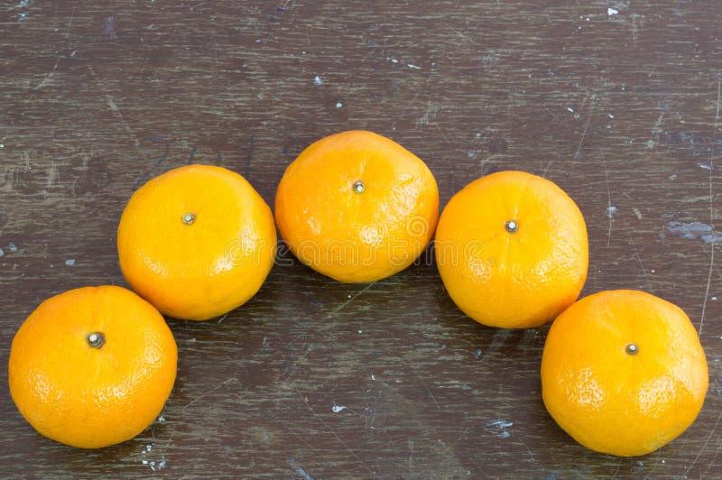 Mogna nya apelsiner på träbakgrund för mörk brunt arkivbild