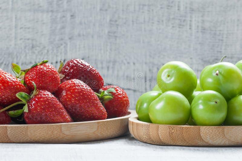 Mogna nya jordgubbar och gröna plommoner i bambubunke på vit träbakgrund arkivbilder