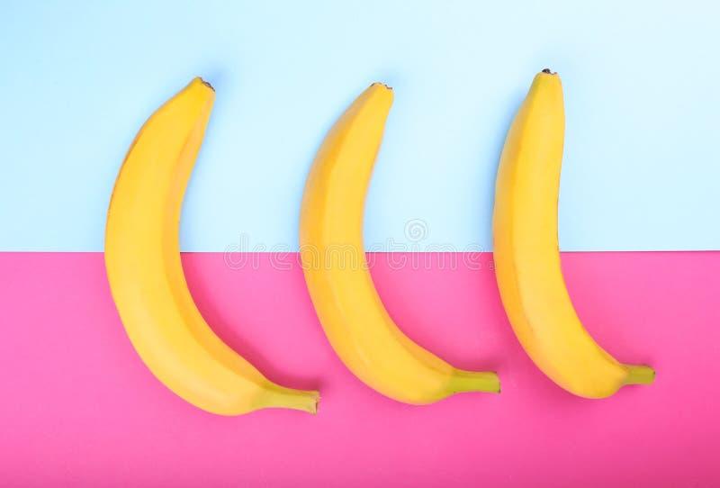 Mogna, nya och söta gula bananer på ljust rosa färger och ljus - blå bakgrund tropiska bananer Banan närbild arkivfoto