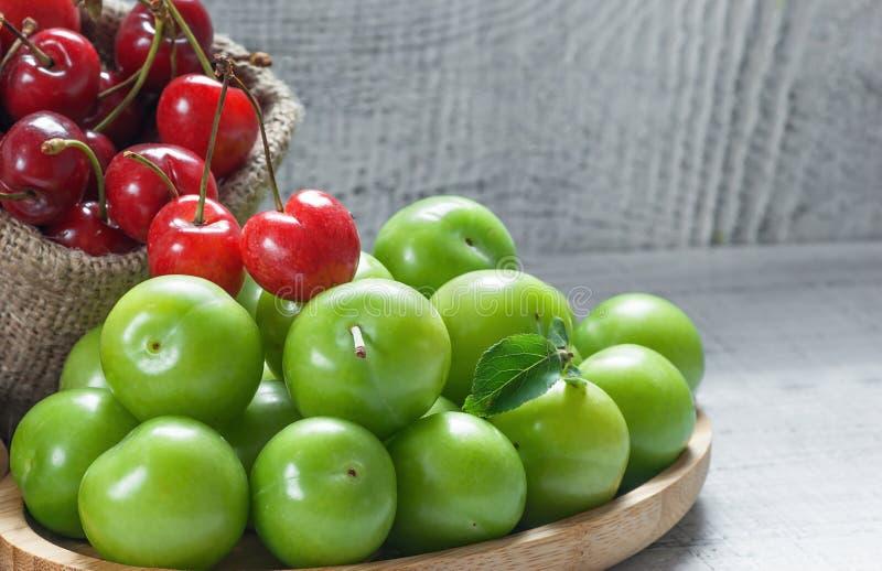 Mogna nya röda körsbär och gröna plommoner i bambubunke på vit träbakgrund arkivbild