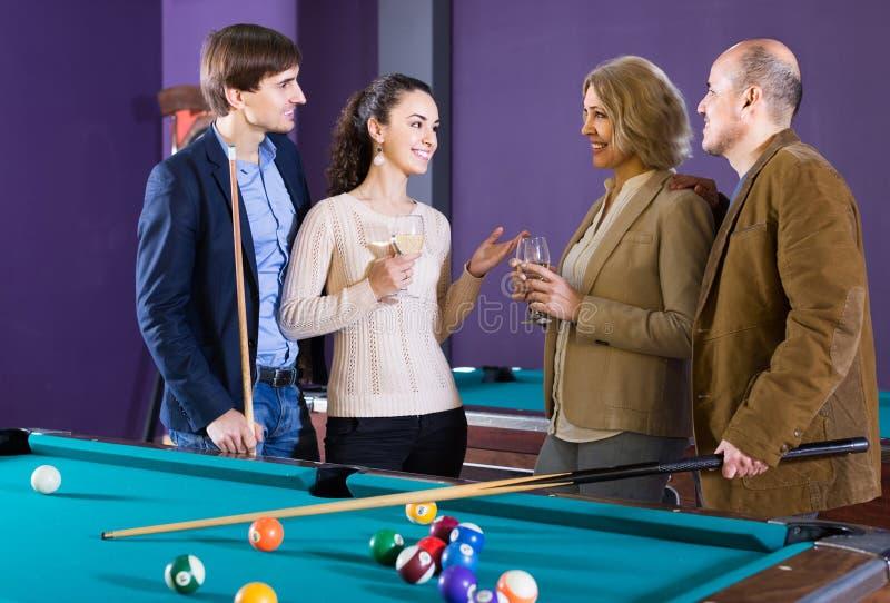 Mogna och unga par som ut tillsammans hänger i billiardklubba royaltyfri bild