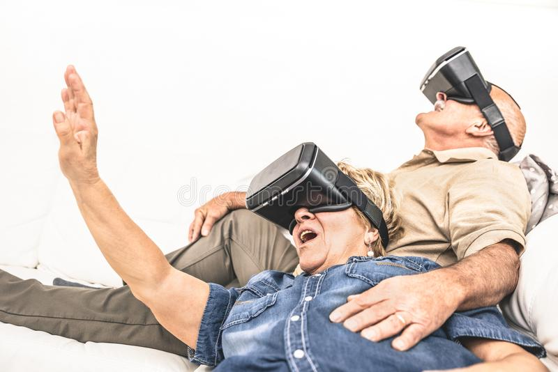 Mogna par för pensionär som har gyckel samman med virtuell verklighet honom royaltyfri fotografi