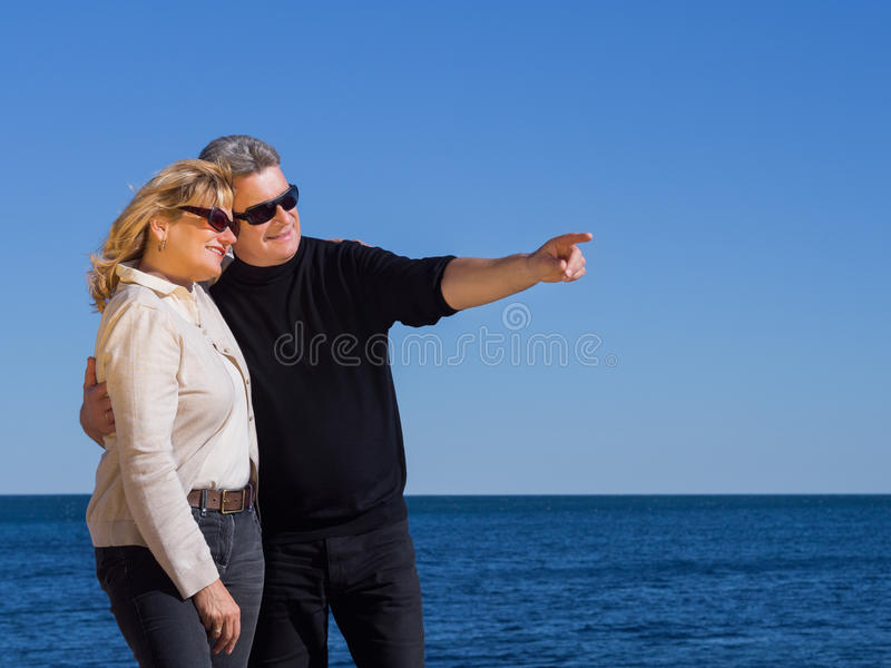 Mogna par för romantiker som pekar till copyspace på kusten royaltyfri foto