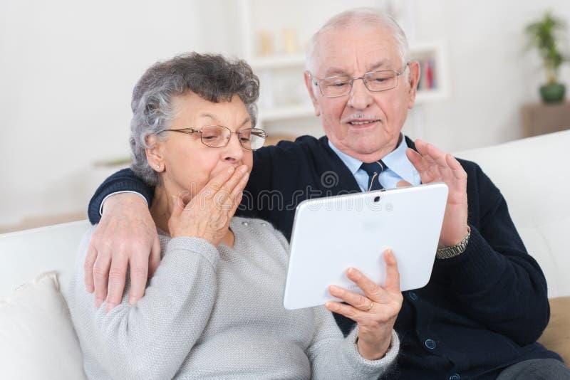 Mogna par genom att använda den digitala minnestavlan i deras lägenhet arkivfoto
