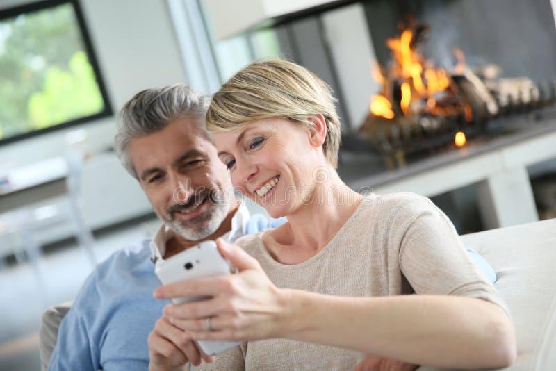 Mogna par genom att använda smartphonen arkivbild
