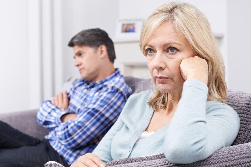 Mogna par med förhållandesvårigheter som sitter på soffan royaltyfria foton