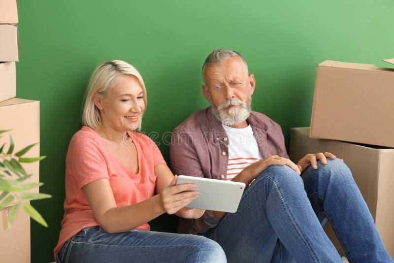 Mogna par med minnestavladatoren som inomhus sitter på golv nära askar flytta sig f?r hus som ?r nytt arkivbilder