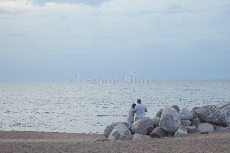 Mogna par på den sandiga kusten av sjön arkivbilder