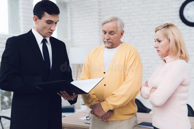 Mogna par på ett mottagande med en advokat Advokaten läser ett dokument Gamla människor är uppriven royaltyfria bilder