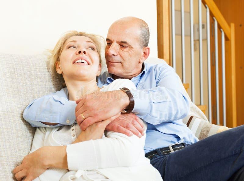 Mogna par på soffan i hemmiljö royaltyfria foton