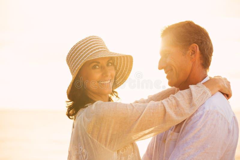 Mogna par som är förälskade på stranden på solnedgången fotografering för bildbyråer