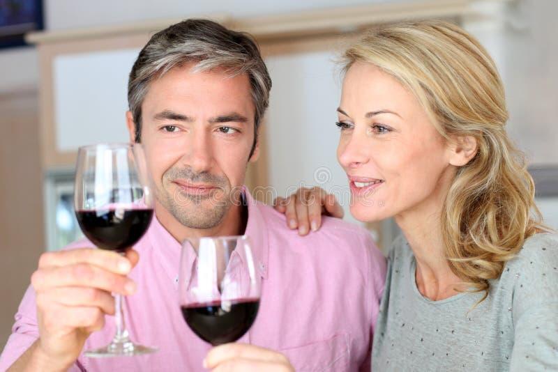 Mogna par som dricker rött vin royaltyfri fotografi