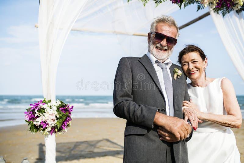 Mogna par som får att gifta sig på stranden royaltyfri foto