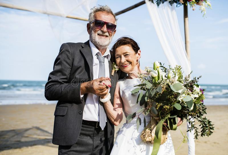 Mogna par som får att gifta sig på stranden royaltyfria bilder