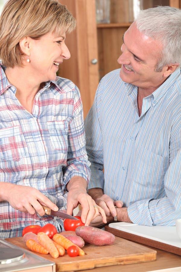 Mogna par som förbereder grönsaker royaltyfri fotografi