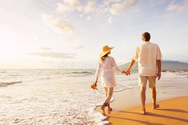 Mogna par som går på stranden på solnedgången royaltyfri bild