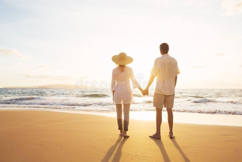 Mogna par som går på stranden på solnedgången royaltyfri foto