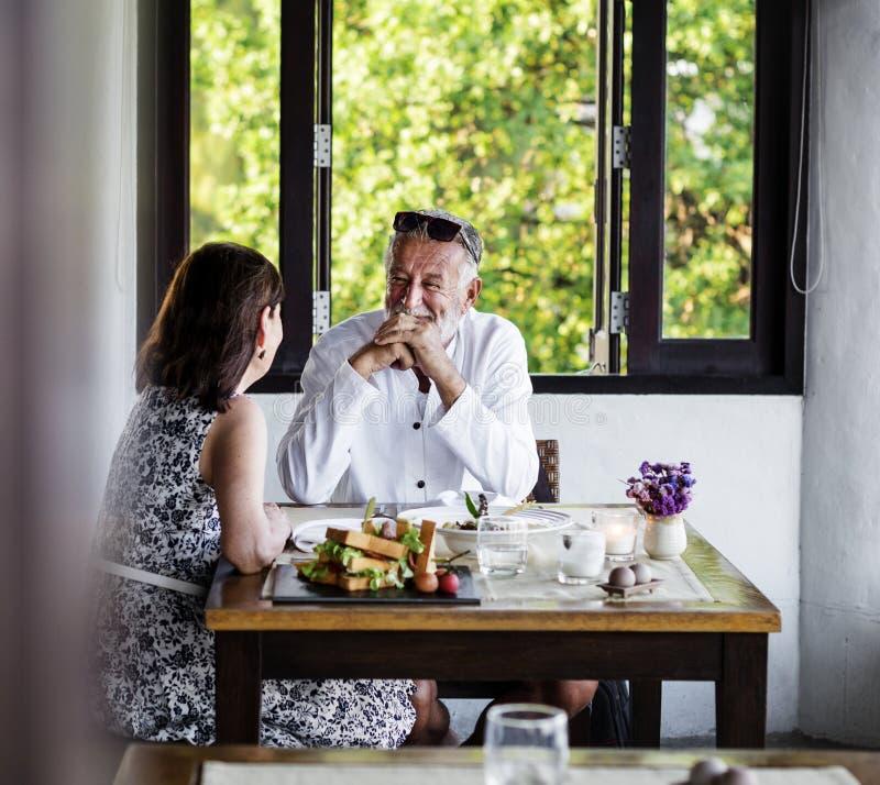 Mogna par som har lunch på en restaurang royaltyfri bild