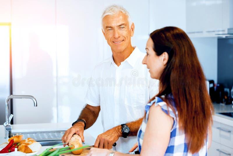 Mogna par som hemma lagar mat royaltyfri foto