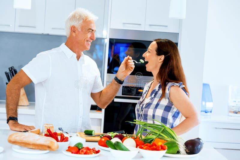 Mogna par som hemma lagar mat royaltyfria bilder