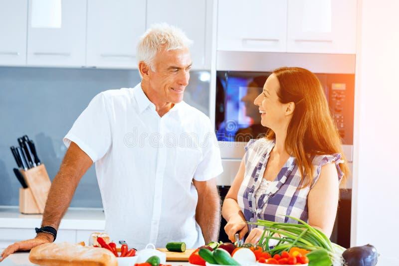 Mogna par som hemma lagar mat arkivbilder