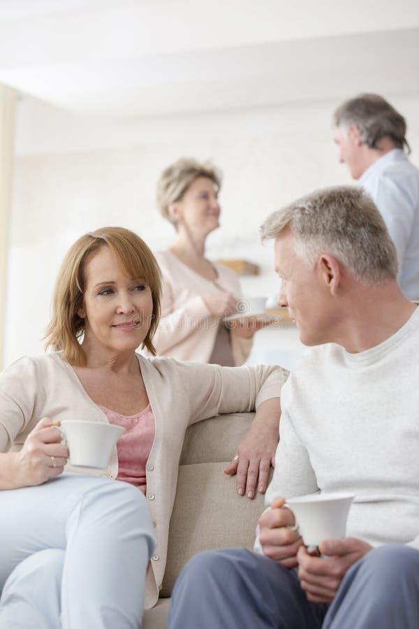 Mogna par som hemma talar i vardagsrum royaltyfri fotografi