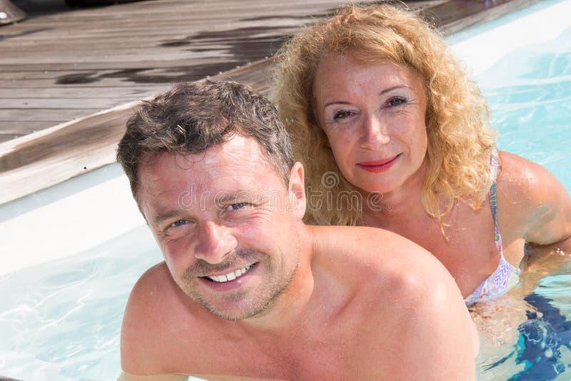 Mogna par som kopplar av i simbassäng royaltyfria foton