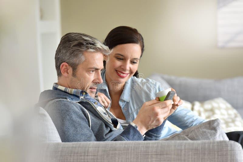 Mogna par som kopplar av i soffa royaltyfri fotografi