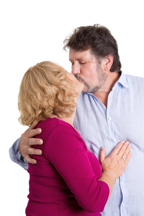 Mogna par som kysser - mannen och kvinnan som isoleras på den vita backgrouen royaltyfri fotografi